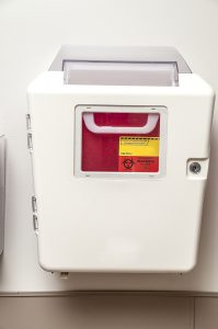 Sharps container on the wall of a patient room in a hospital or doctors office